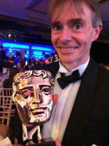 Paul Fletcher holding BAFTA award