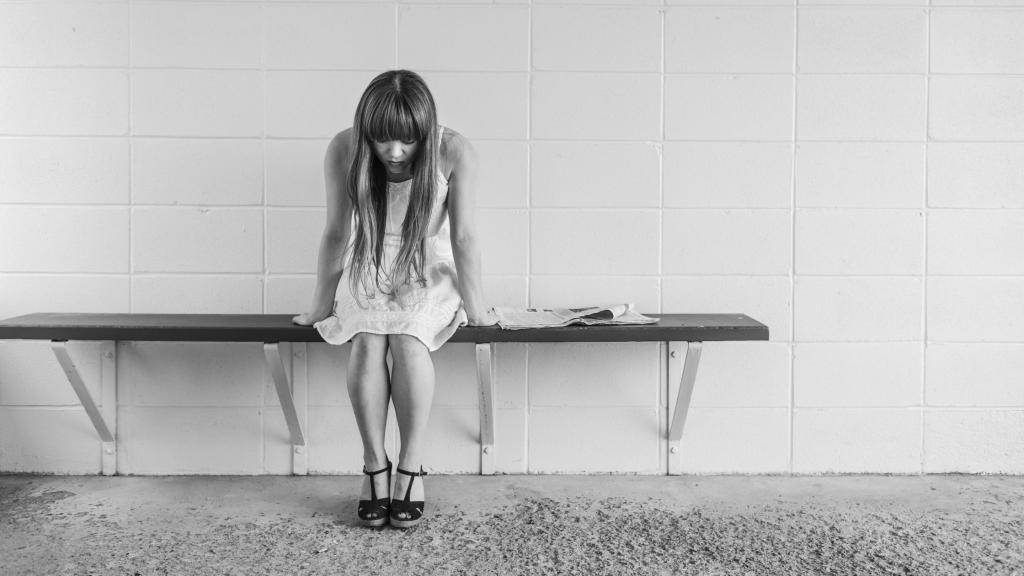 grey girl sitting on bench worried